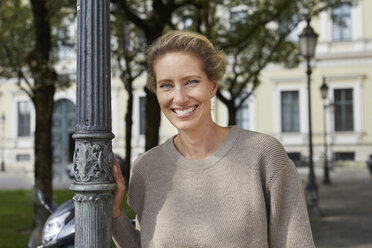 Portrait of smiling woman leaning against lamp post in the city - PNEF01427