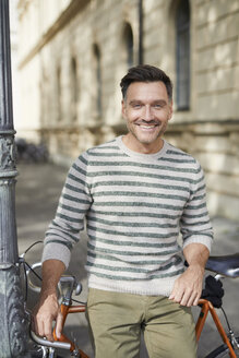 Portrait of smiling man with bicycle in the city - PNEF01430