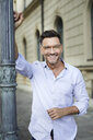 Portrait of smiling businessman leaning against lamp post in the city - PNEF01436