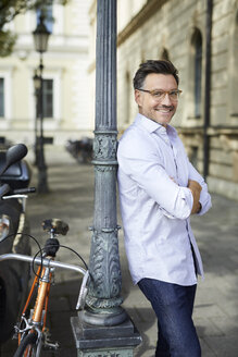 Portrait of smiling businessman with bicycle leaning against lamp post in the city - PNEF01439