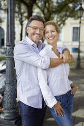 Portrait of happy couple embracing in the city - PNEF01442