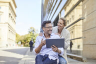 Happy couple using tablet in the city - PNEF01448