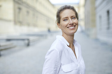 Portrait of smiling woman wearing white shirt in the city - PNEF01454