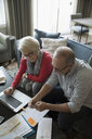 Senior couple with credit card and laptop paying bills online in living room - HEROF31486