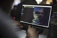 Reflection of male hacker coding working hackathon at laptop - HEROF31534