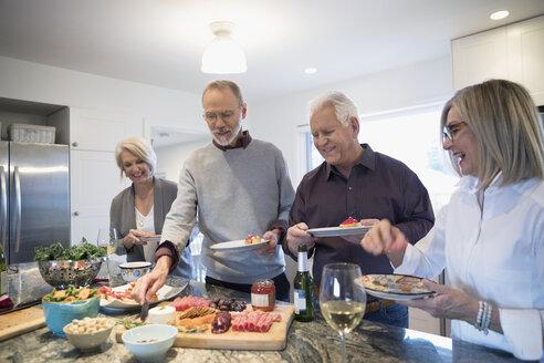 Senior couples enjoying appetizers in kitchen - HEROF31555