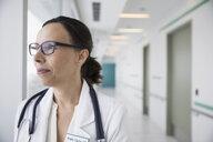 Portrait pensive female doctor looking away in clinic corridor - HEROF31630