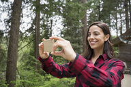 Woman photographing woods with camera phone - HEROF31671