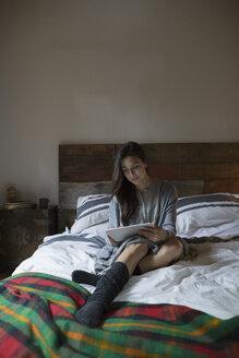 Woman relaxing on bed using digital tablet - HEROF31680