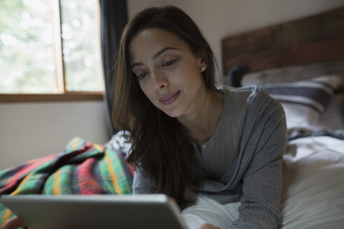 Woman laying on bed using digital tablet - HEROF31683