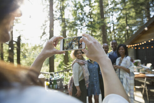 Woman with cell phone photographing friends at party on cabin balcony in woods - HEROF31689