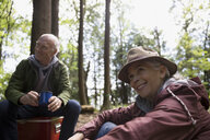 Smiling senior couple drinking coffee at campsite in woods - HEROF31701