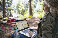 Woman drinking coffee using laptop at campsite in woods - HEROF31704