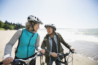 Smiling women on bicycles on sunny beach - HEROF31713