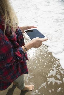 Woman using digital tablet in ocean surf - HEROF31716