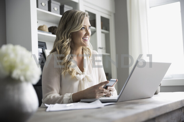 Smiling woman texting with cell phone at laptop in home office - HEROF31743