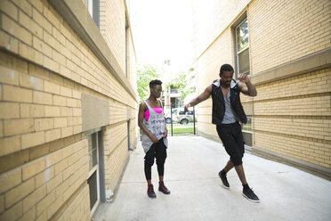 Young woman watching man dancing in urban alley - HEROF31776