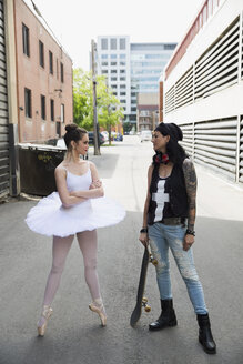 Young ballerina confronting cool skateboarder in urban alley - HEROF31779
