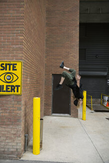 Young man doing parkour backflipping off urban brick wall - HEROF31782