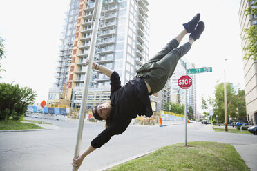 Young man doing parkour on pole in urban street - HEROF31785