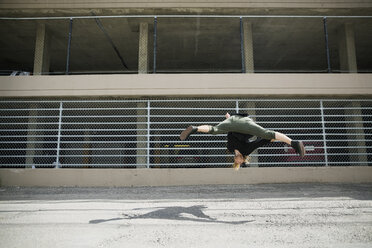 Young man doing parkour against fence in urban alley - HEROF31791