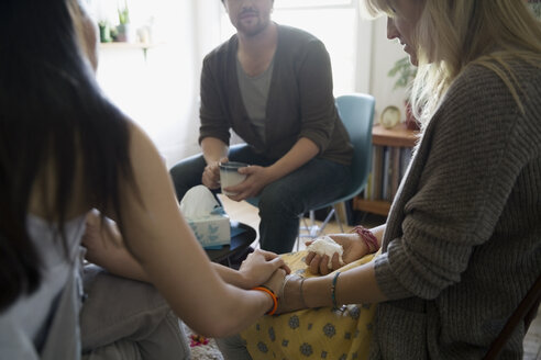 Support group holding hands meeting in living room - HEROF31806