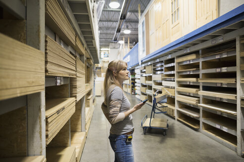 Woman with cell phone shopping for plywood in home improvement store - HEROF31827