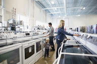 Young family shopping for stoves in appliance store - HEROF31860