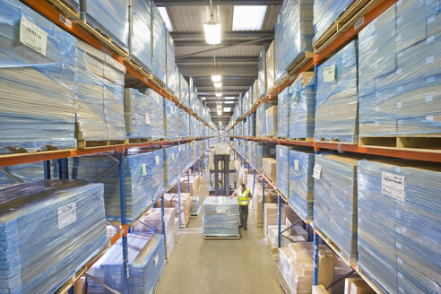Warehouse worker inspecting boxes on forklift - JUIF00467