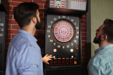 Two men playing darts setting electronic dartboard - ZEDF02017