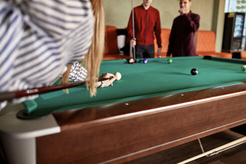 Young woman playing billiards with friends - ZEDF02023