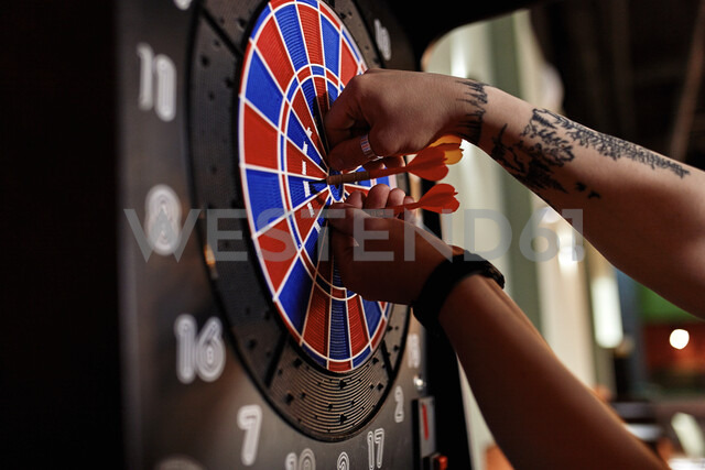 Close-up of tattooed man taking out darts from electronic dartboard - ZEDF02026