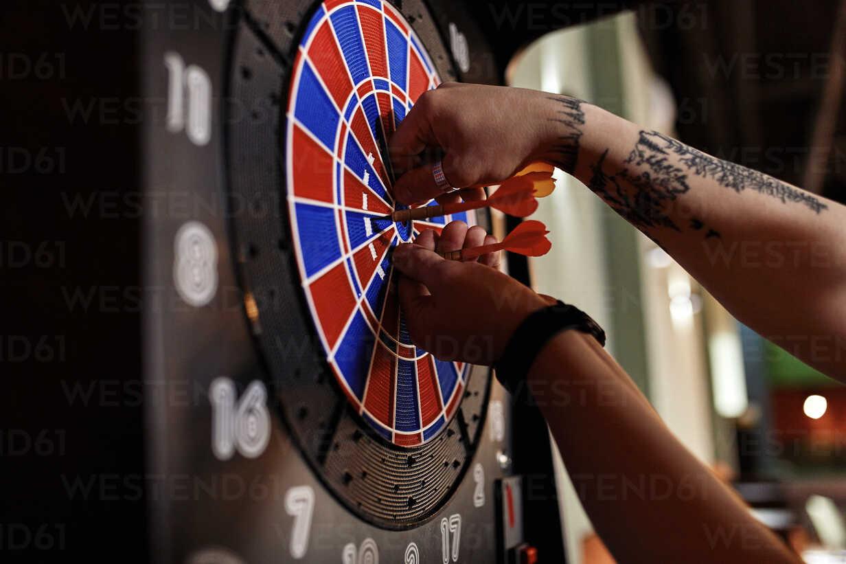 Close-up of tattooed man taking out darts from electronic dartboard - ZEDF02026 - Zeljko Dangubic/Westend61