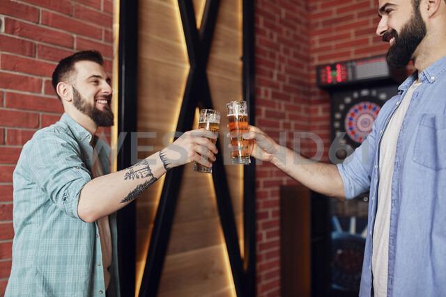 Two happy friends clinking beer glasses at dartboard in a pub - ZEDF02029 - Zeljko Dangubic/Westend61