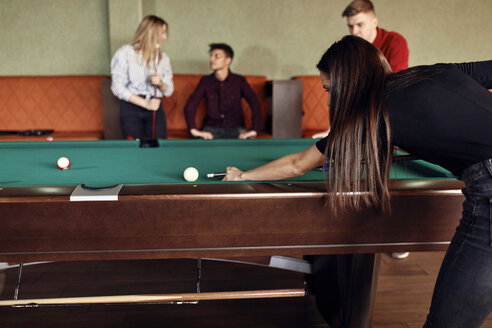 Young woman playing billiards with friends - ZEDF02038