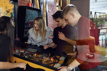 Man playing pinball watched by friends - ZEDF02065