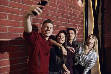 Happy friends taking a selfie with smartphone at brick wall - ZEDF02074