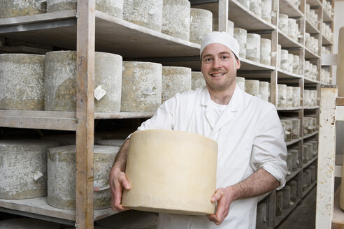 Portrait of smiling cheese maker holding large farmhouse cheddar cheese wheel in cellar - JUIF00521