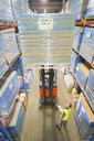 Manager watching warehouse worker moving boxes on forklift - JUIF00545