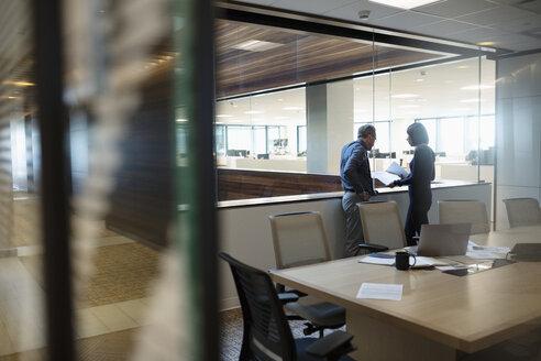 Business people reviewing paperwork in conference room meeting - HEROF31886
