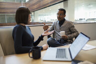 Business people drinking coffee and talking in conference room meeting - HEROF31889