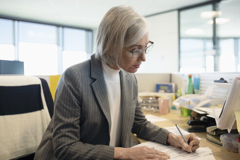 Focused senior businesswoman doing paperwork at desk in office cubicle - HEROF31895