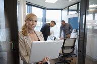 Portrait confident businesswoman with laptop in conference room doorway - HEROF31949
