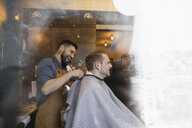 Smiling male barber fastening salon cape on client in barbershop - HEROF32069