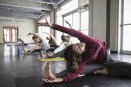 Woman practicing wide legged seated side bend in yoga class studio - HEROF32102