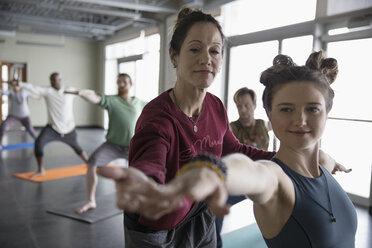 Yoga teacher adjusting shoulders of female student practicing yoga warrior 2 pose in yoga class - HEROF32105