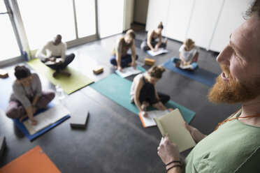 Yoga teacher talking to students with journals on yoga mats in yoga class studio - HEROF32114
