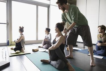 Yoga instructor adjusting shoulder - HEROF32117