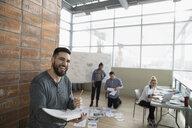 Smiling creative male designer brainstorming in office - HEROF32123