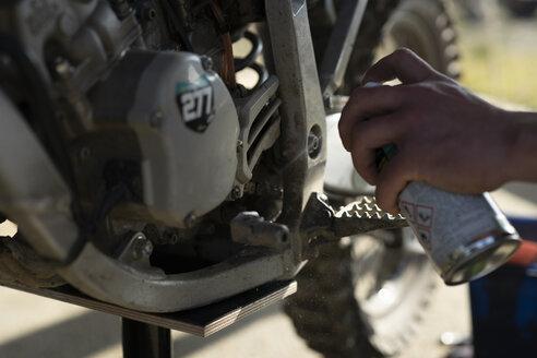 Close-up of man working on motocross bike - FBAF00346